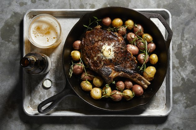 Skillet with large tomahawk steak & potatoes, overhead view