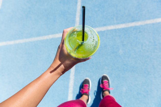 Runner drinking a green smoothie on running track before a marathon