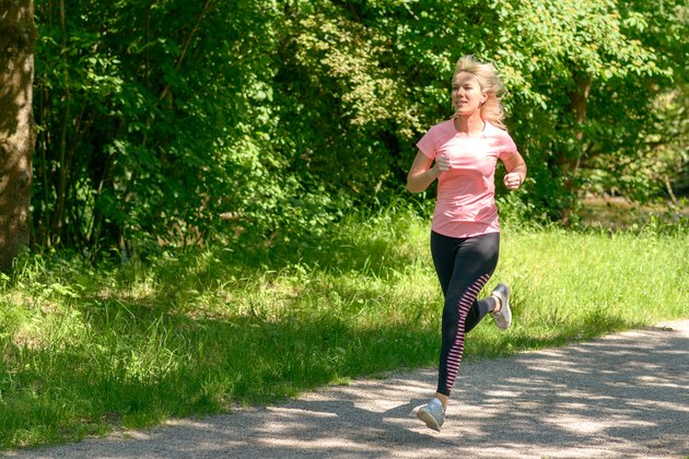 Woman Running On Footpath While Exercising In Park