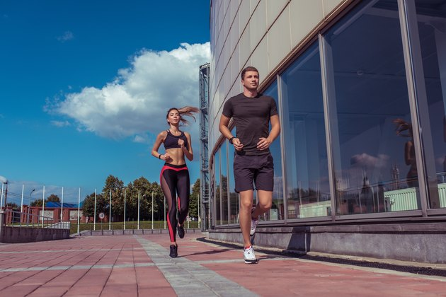 Athletic couple man and girl in summer city, run on morning run, burning calories, cardio fitness training day and morning. Healthy lifestyle style. Sportswear, friends and relationships are paired.