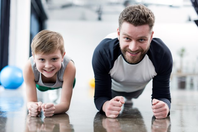 Man and boy doing plank exercise at fitness center
