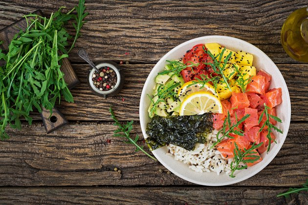Hawaiian salmon fish poke bowl with rice, avocado, mango, tomato, sesame seeds and seaweeds. Buddha bowl. Diet food. Top view. Flat lay