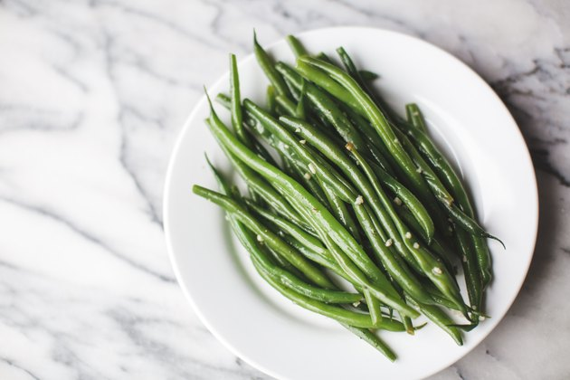 Cooked green beans on a white plate