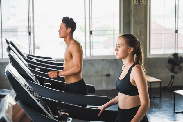 Young couple exercising by running on the treadmill to maintain good health