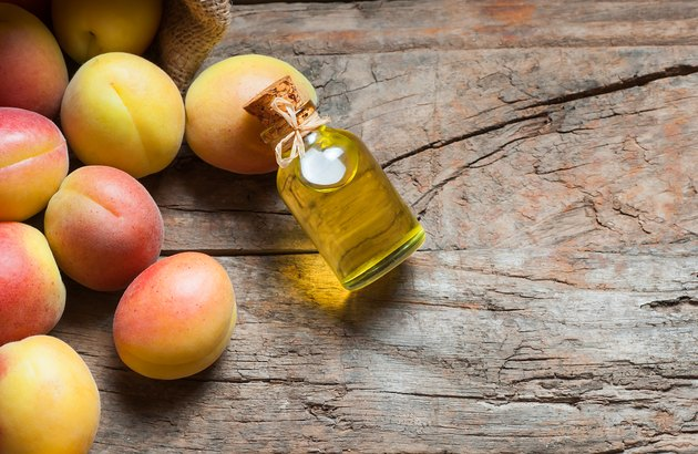 Glass bottle of Apricot seed kernel oil ( prunus armeniaca oleum ) with fresh ripe apricot fruits on wooden rustic background