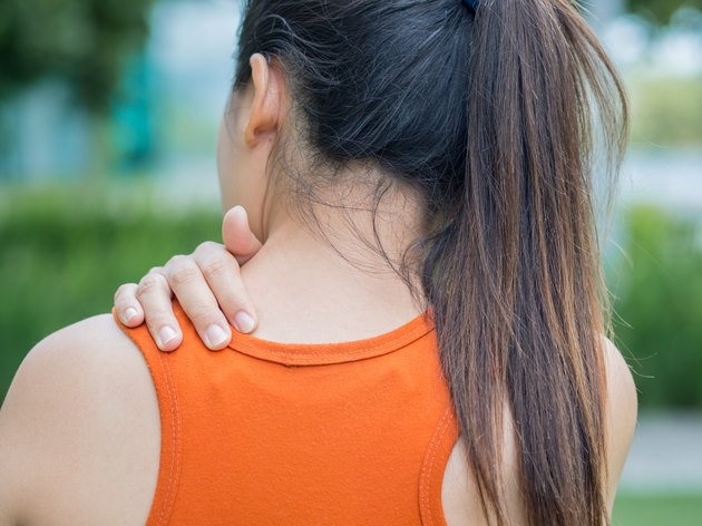 Closeup sport woman feel pain on her neck and shoulder, health care concept.