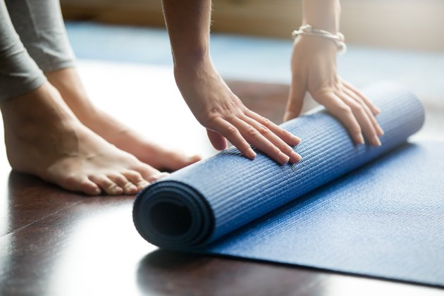 woman rolling up blue yoga mat on wooden floor with bare feet