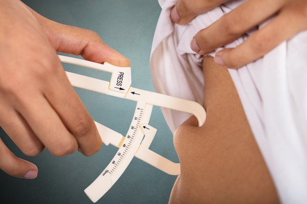 Woman Checking Stomach Fat With Caliper