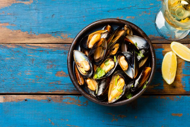 Mussels in clay bowl, glass of white wine and lemon