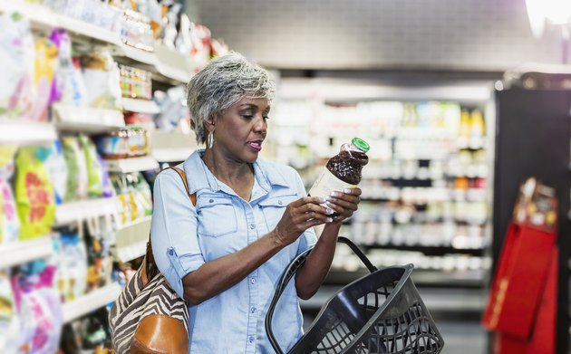 African-American woman in grocery store reading nutrition label