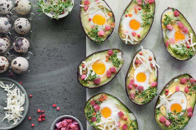 Keto diet dish: Avocado boats with ham cubes, quail eggs, cheese and cress sprouts