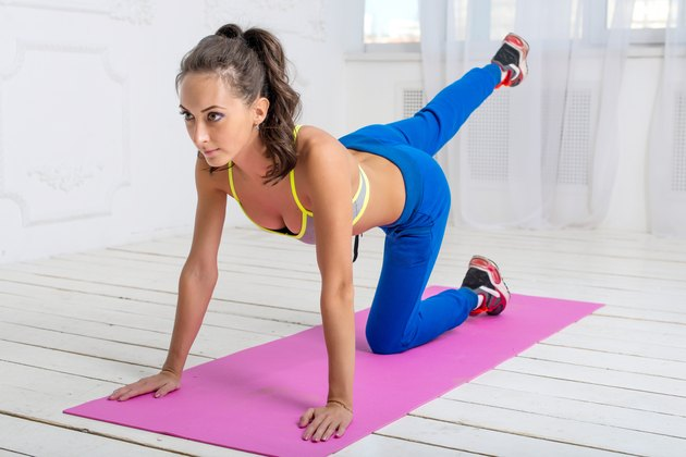Young  dark-haired athletic sporty slim  woman with ponytail workout