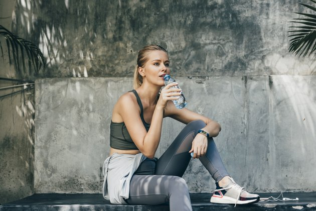 Female jogger sitting at a park and drinking water