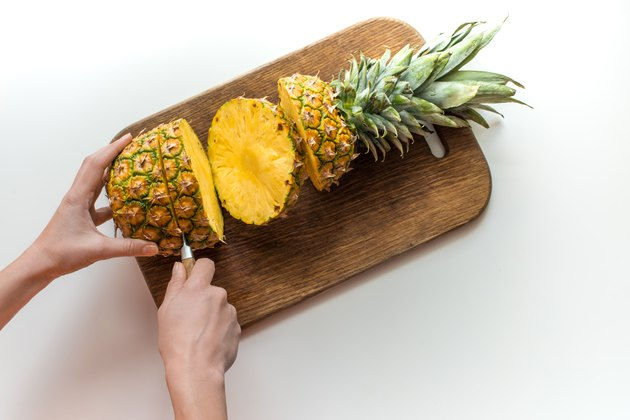 person cutting fresh pineapple on wooden board