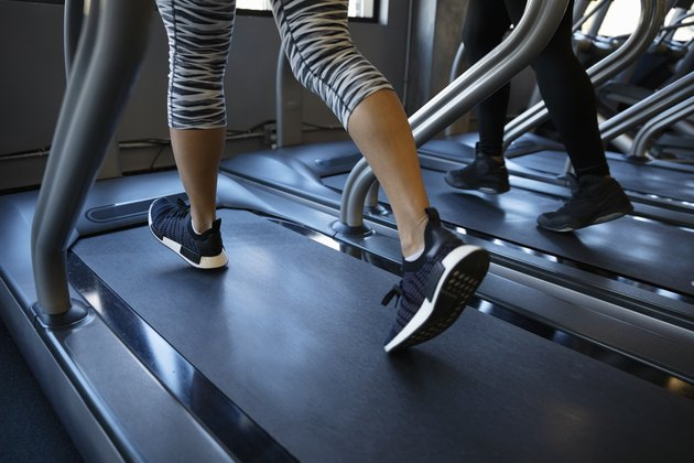 Legs of woman walking on treadmill in gym