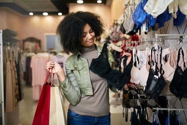 Young smiling attractive african american woman choosing right bra size in lingerie store boutique. Black mixed race pretty girl considers underwear in shop and holding paper shopping bags