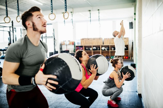 People doing an EMOM workout with medicine balls at a CrossFit box