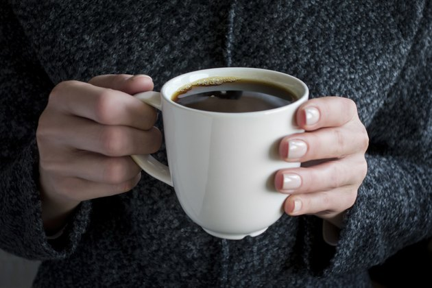 holding a cup of black coffee