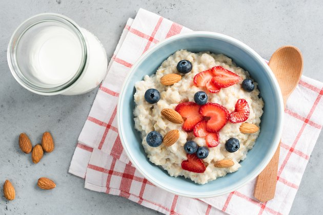 Oatmeal porridge with fresh berries and nuts, top view