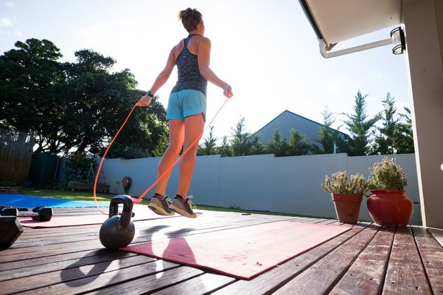 Woman jumping rope with good form to avoid back pain.