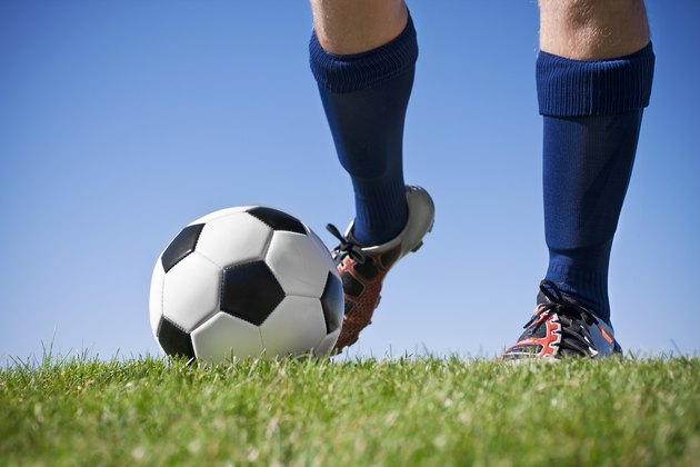 Close up of feet in blue socks kicking a soccer ball
