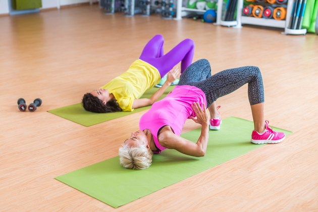 Women training their glutes by doing bridging exercise on mats