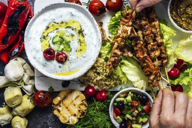 Hand taking chicken skewers from a board with lots of snacks and a bowl of yogurt and cucumber dip for savory yogurt recipes.
