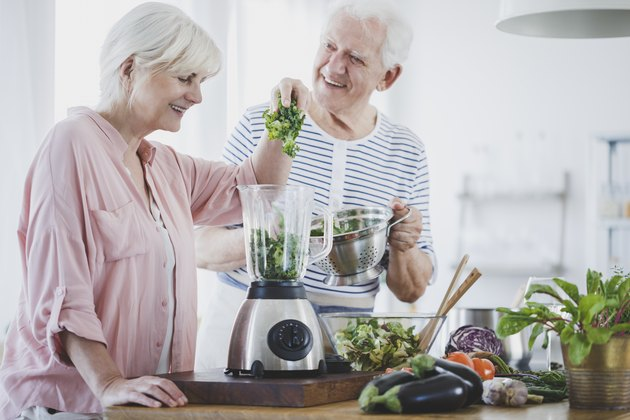 Happy older couple on a diabetes diet preparing a smoothie at home