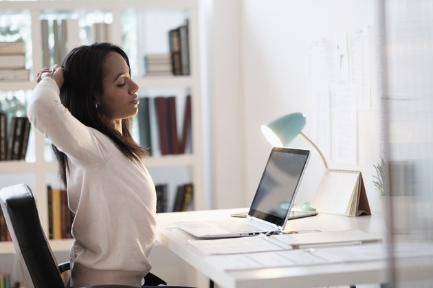 Mixed race businesswoman stretching at desk