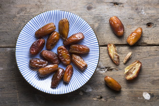 An overhead bowl of dates on a rough wooden background