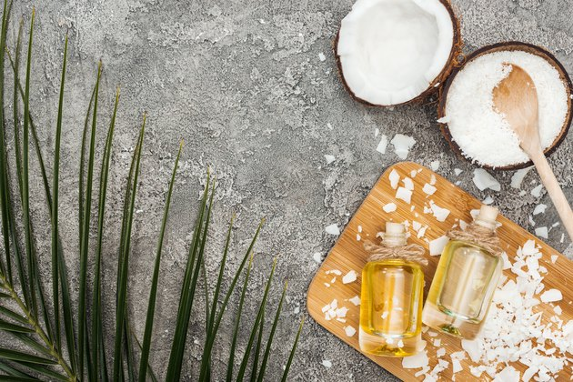 top view of coconut oil in bottles on wooden board on grey textured background with copy space and palm leaf