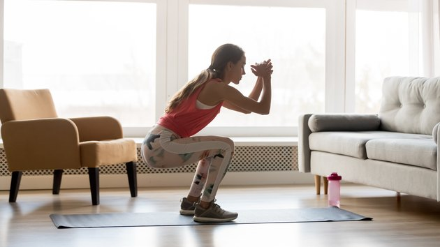 woman doing body-weight squat exercise in living room