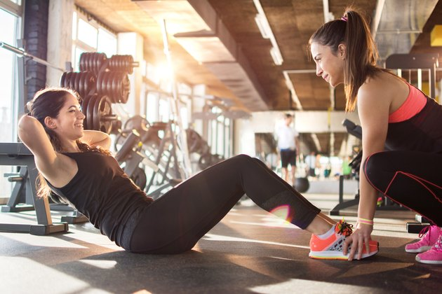 Young woman exercising sit-ups with assistance of female friend in gym