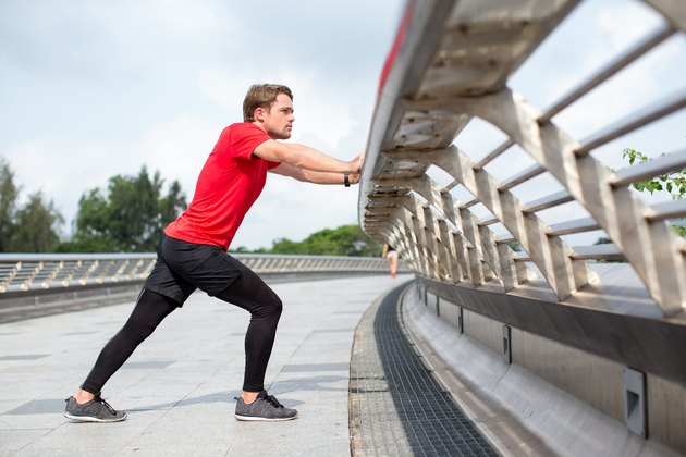 Serious Man Stretching Calf and Leaning on Railing