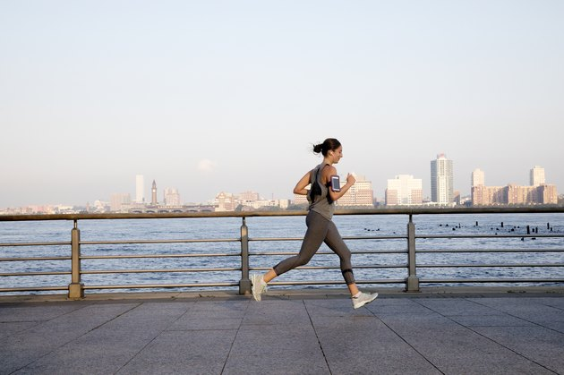 Young woman running along Hudson River