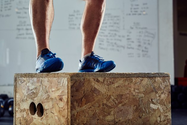 Closeup of athlete doing box jump at the gym