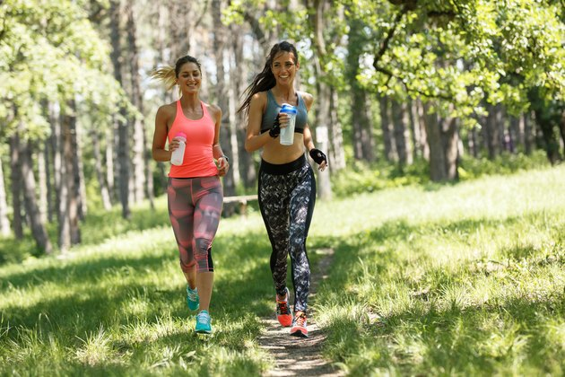 Two young female friends jogging trough the forest.