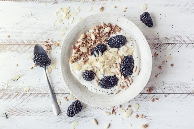 Breakfast bowl with homemade granola, dried fruits, blackberries and almond yogurt