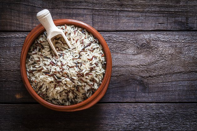 Brown bowl filled with mixed rice shot from above on rustic wooden table