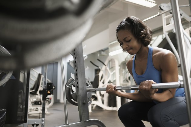 Woman doing barbell biceps curls at the gym