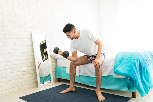 Man performing dumbbell biceps curl on edge of bed as a weight bench alternative.
