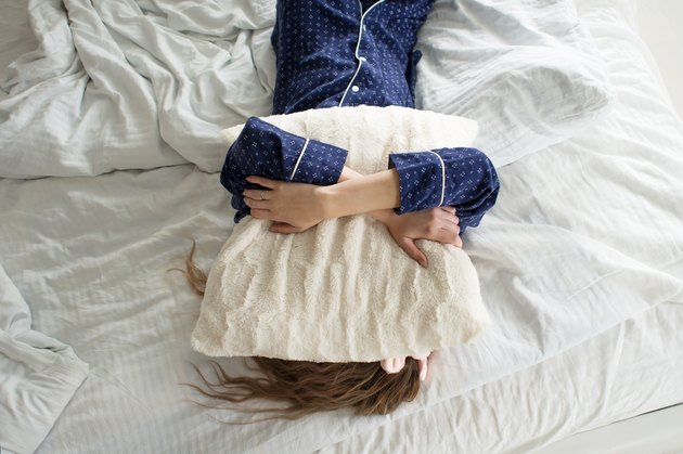 A woman in bed, covering her face with a pillow, suffering from insomnia due to gut problems