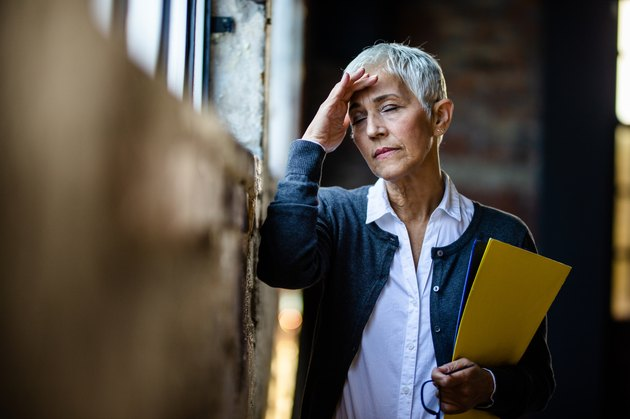 Senior businesswoman experiencing a headache from low sodium levels