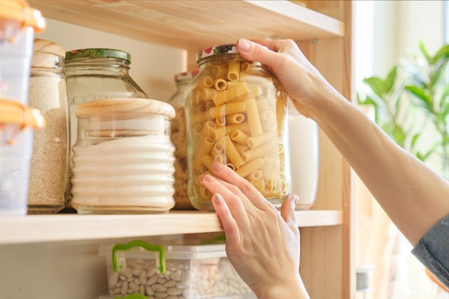 Food products in the kitchen. Woman taking jar of pasta
