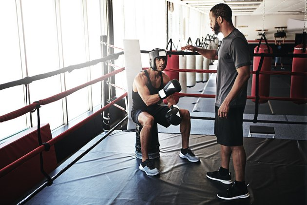 man with his boxing coach in a boxing ring during a boxing lesson