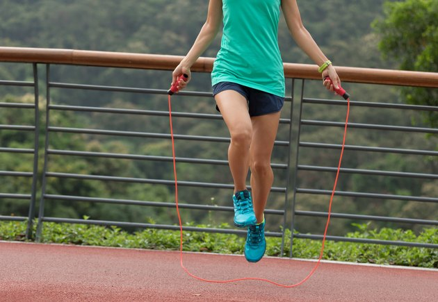 Woman athlete jumping rope on spring forest trail. woman fitness workout wellness concept.