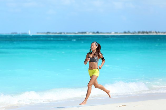 Woman runner running on beach - summer exercise