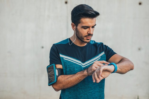 Jogger using a smart watch to measure heart rate while running