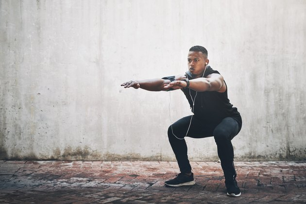 man wearing black workout clothes and headphones doing body-weight squat outside in front of gray wall