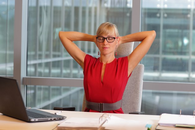 caucasian business woman in eyeglasses relaxing neck,stretching arms